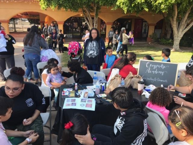 Compadre Academy students paint faces during Guad Xmas party